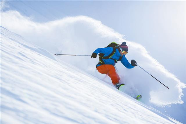 Female Athlete Skiing In Deep Powder